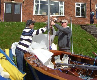 A sailing instructor shows a trainee how to rig up a dinghy