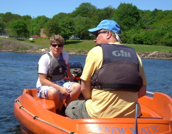 Sailing instructors in an orange powerboat keeping watch over beginner sailors