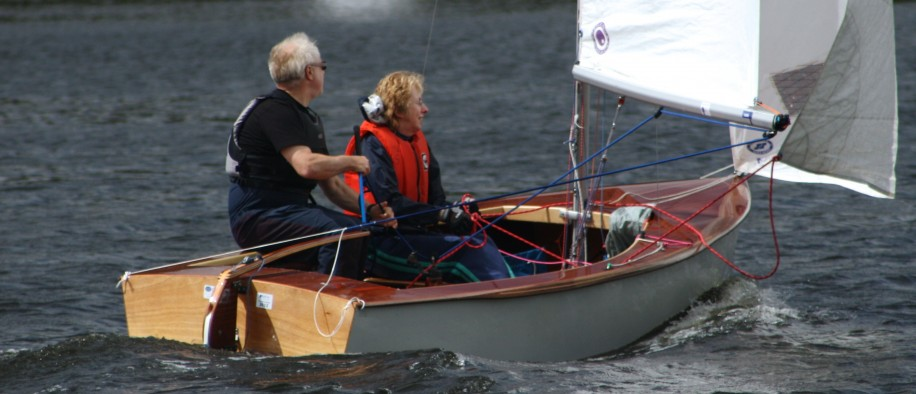 An instructor demonstrates sailing a dinghy downwind to a novice crew