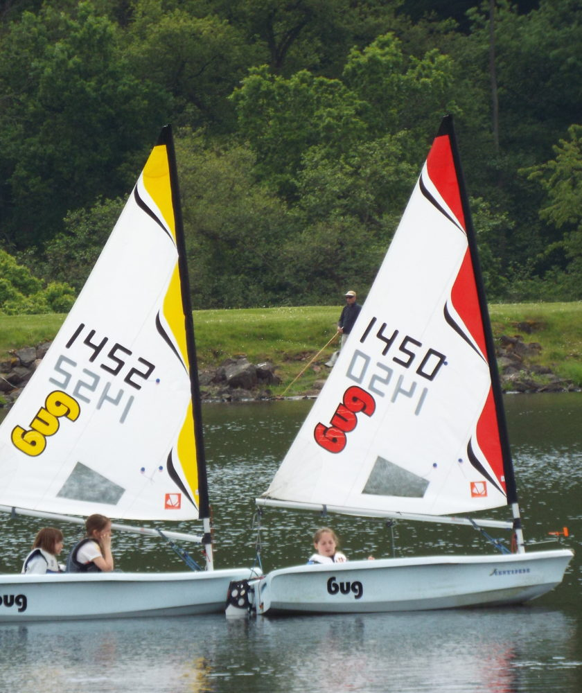 Three children learning to sail in Laser Bug dinghies